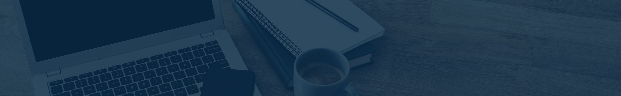 Image of a table top with notebook, coffee and laptop open